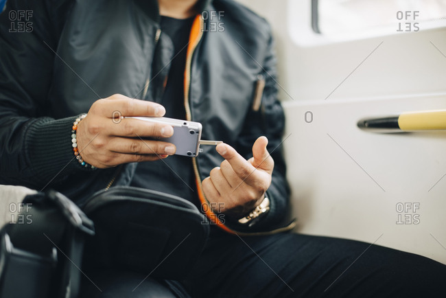 Man doing blood test with glaucometer while sitting in train