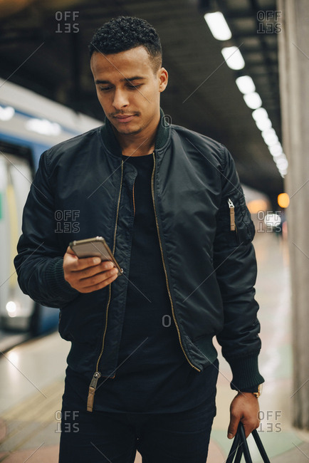 Man using mobile phone while standing by train at subway station