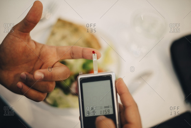Businessman using glaucometer in blood test while having food at table