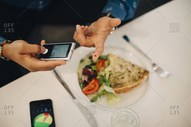 Businessman checking blood sugar level with glaucometer while having food at table