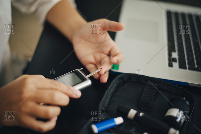 Cropped hands of businesswoman checking blood sugar level with glaucometer at desk