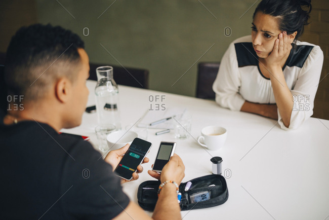 Colleague looking at businessman doing blood sugar test while sitting at table during coffee break