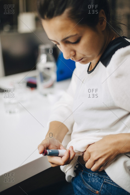 Businesswoman injecting insulin while sitting at table