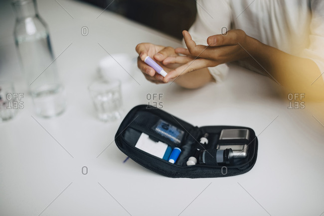 Cropped image of businesswoman doing blood sugar test at table in office