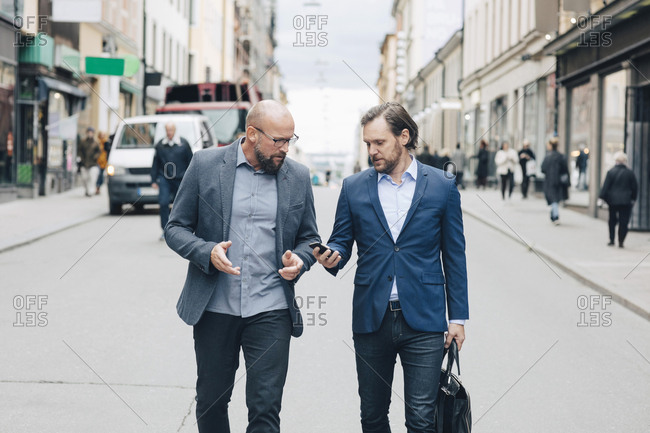 Business people discussing while walking on street in city