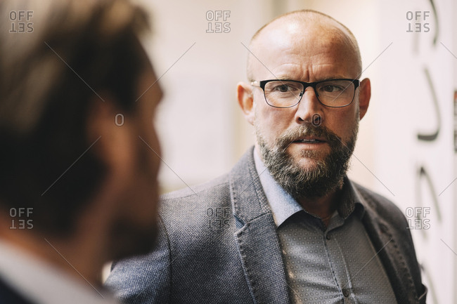 Close-up of businessman discussing with colleague at office