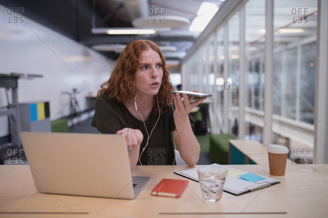 Female executive talking on mobile phone at desk in office