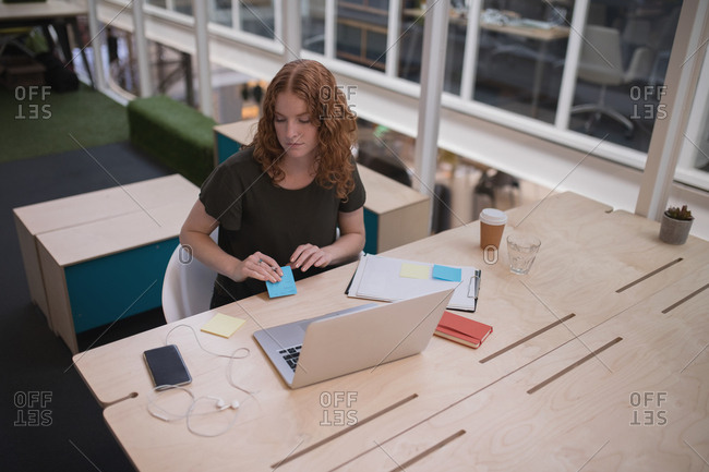 Female executive holding sticky note at desk in office