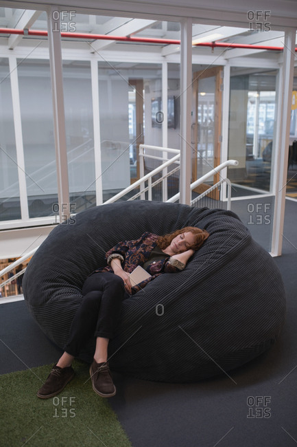 Female executive sleeping on couch in office