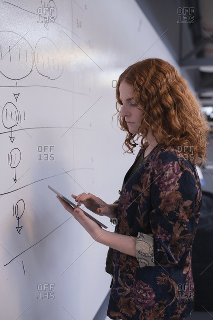 Female executive using digital tablet near whiteboard in office