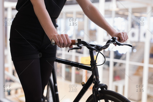 Mid section of female executive walking with cycle in office