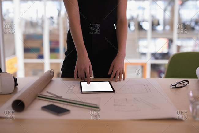 Mid section of female graphic designer using digital tablet in office