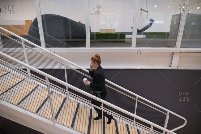 Female graphic designer using mobile phone in office
