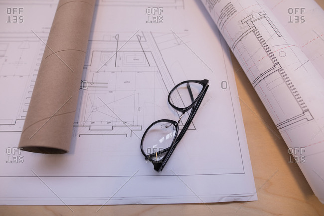 Blueprint and spectacle on table in office