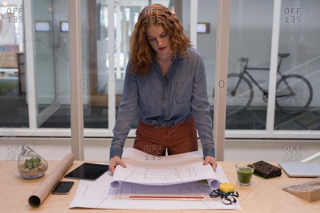 Female graphic designer working on blueprint in office