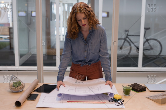 Female graphic designer working on blueprint in office