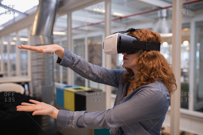 Female executive using virtual reality headset in office
