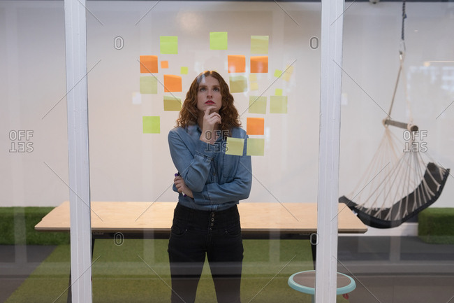 Thoughtful female executive reading sticky notes on glass in office