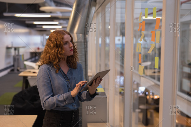 Female executive using digital tablet while reading sticky notes in office