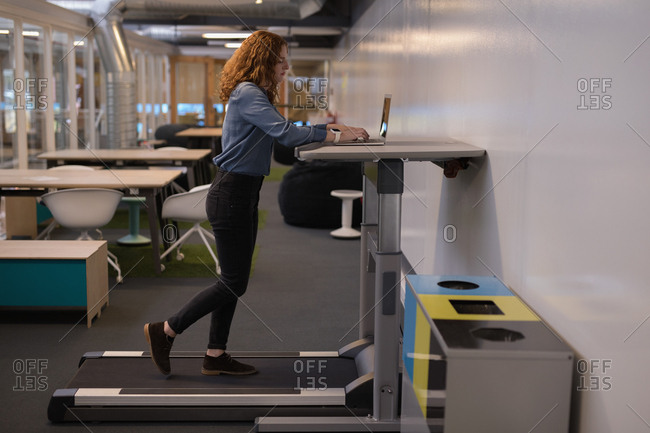 Female executive using laptop on treadmill in office
