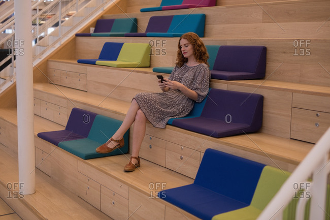 Beautiful female executive using mobile phone in modern office