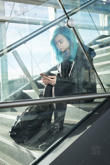 Stylish woman using mobile phone on staircase