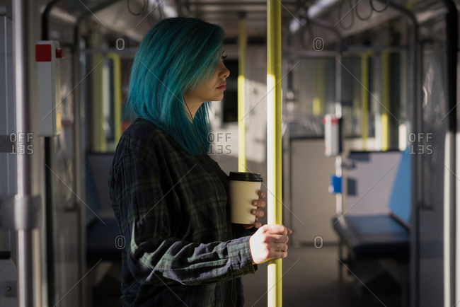 Stylish woman holding coffee cup while travelling in train
