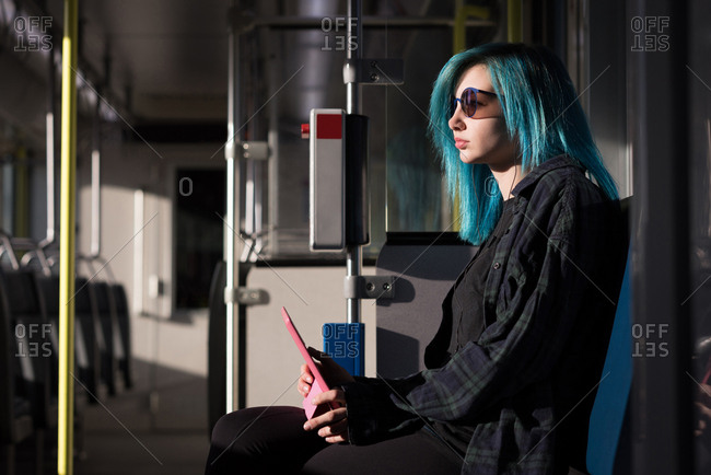 Stylish woman using digital tablet while travelling in train