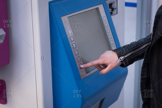 Mid section of woman using ticket vending machine at station