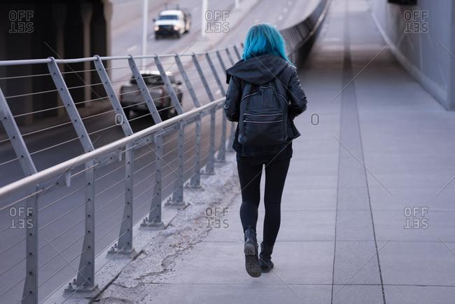 Rear view of stylish woman walking on road