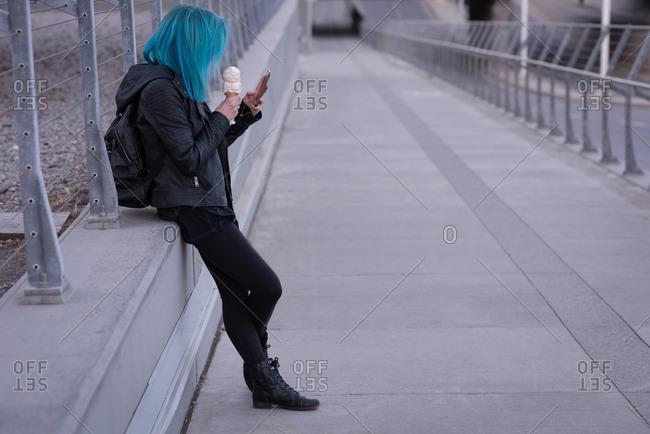 Stylish woman having ice cream while using mobile phone