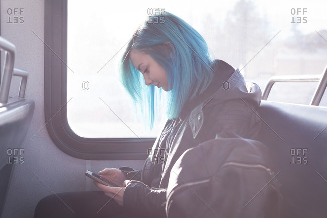 Stylish woman using mobile phone while travelling in train