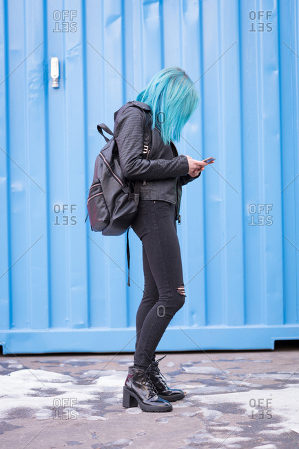 Stylish woman with backpack using mobile phone