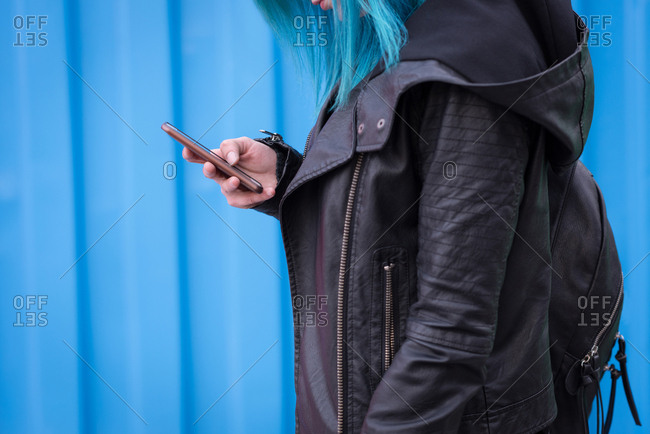 Mid section of woman with backpack using mobile phone