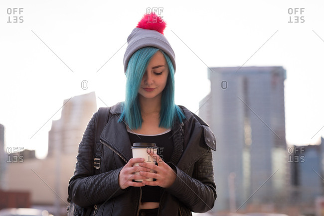 Stylish woman holding disposable cup in city street