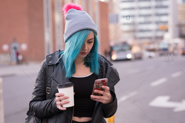 Stylish woman using mobile phone while having coffee in city street
