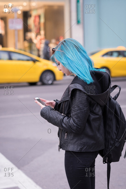 Stylish woman using mobile phone in city street