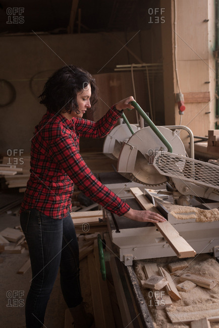 Woman cutting saw with electric saw in carpenter workshop