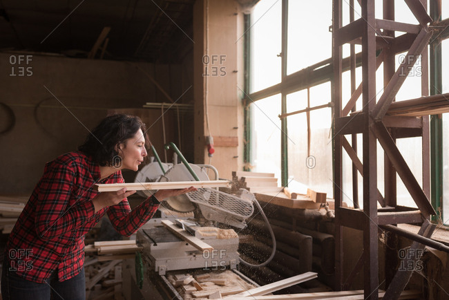 Woman bowling saw dust from plank in carpenter workshop