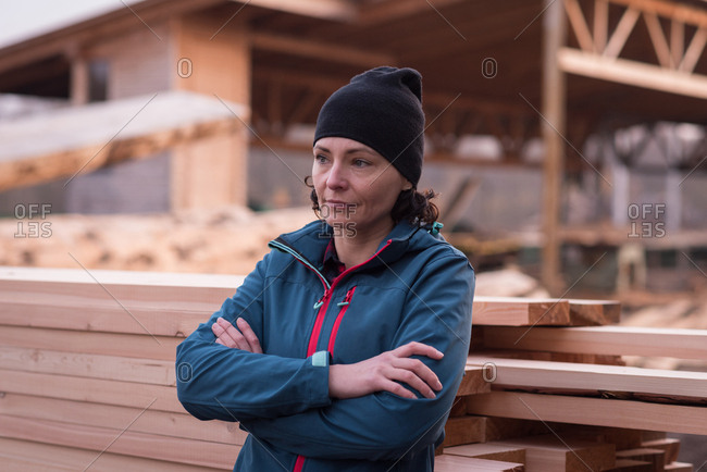 Thoughtful woman standing with arms crossed against wooden plank