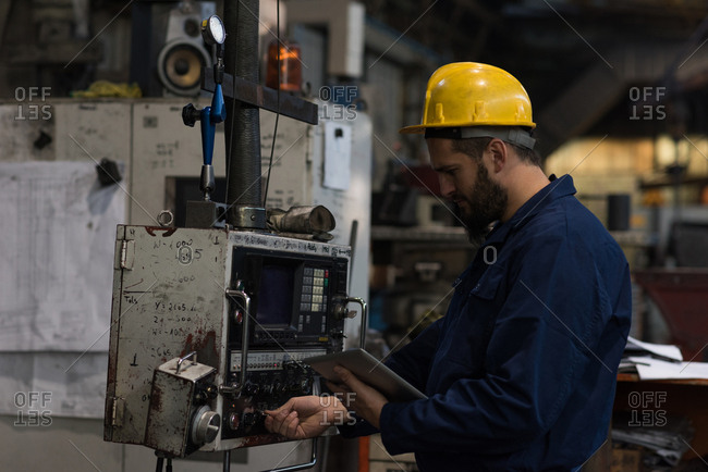 Attentive technician checking machine in metal industry