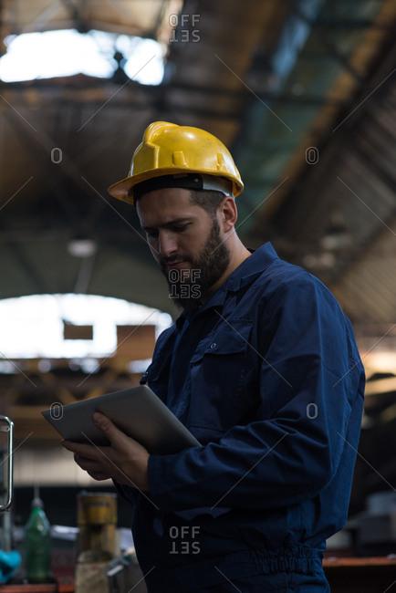 Technician using digital tablet in metal industry