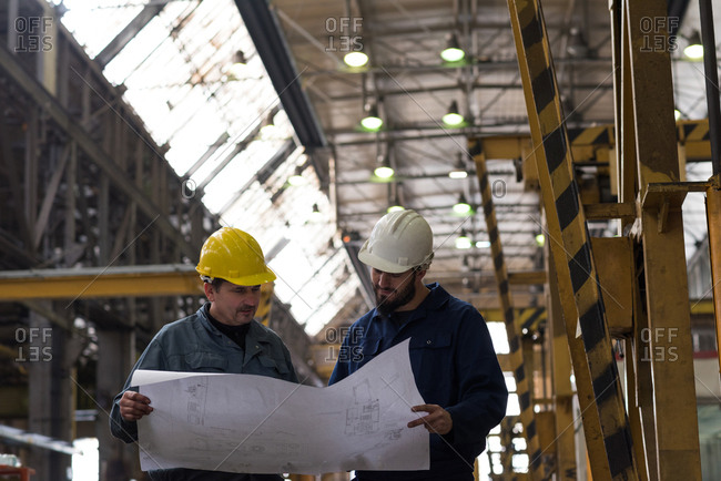 Technician discussing blueprint with his colleague in metal industry