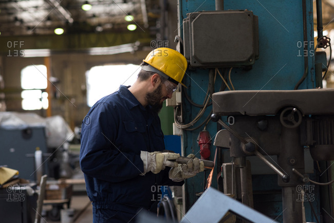 Technician in protective workwear cutting metal in industry