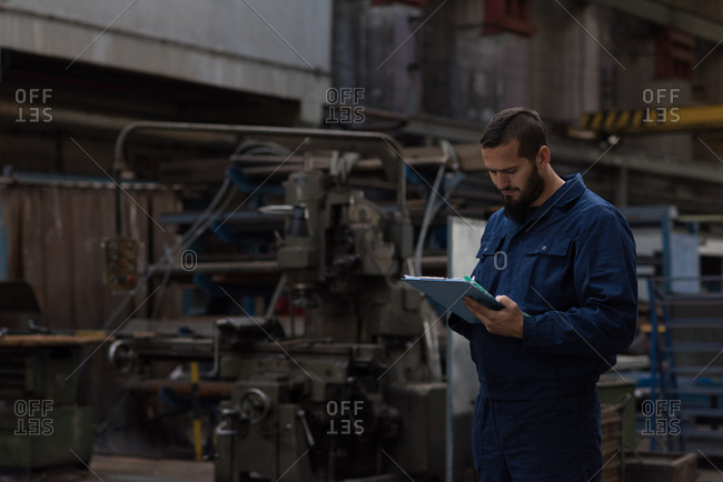 Technician maintaining record on clipboard in metal industry
