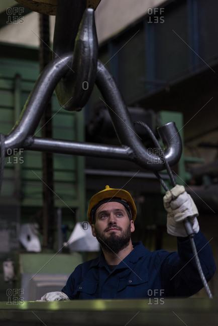 Attentive technician adjusting metal equipment in hook