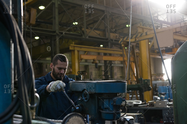 Attentive technician in protective workwear working in metal industry