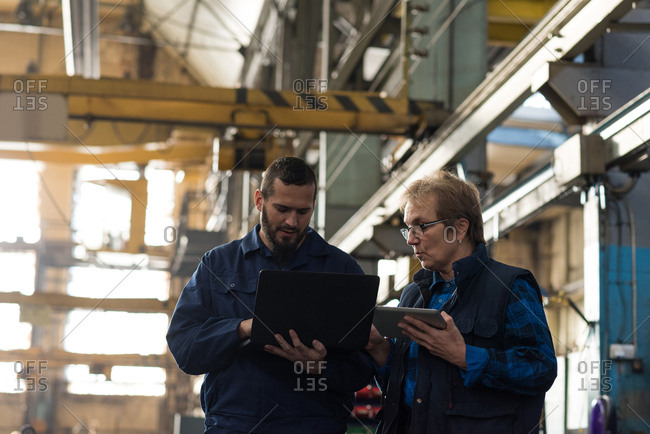 Technicians discussing over laptop in metal industry