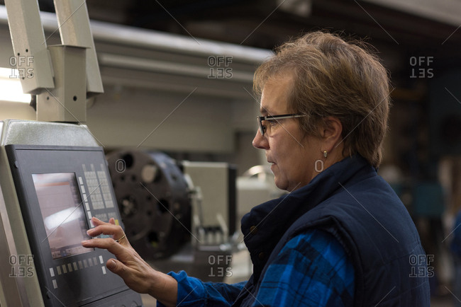 Female technician operating machine in metal industry