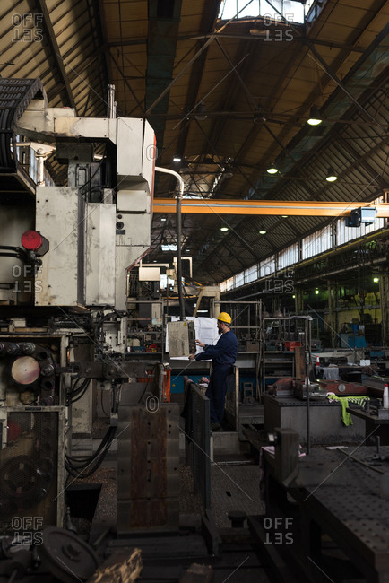 Attentive technician operating machine in metal industry